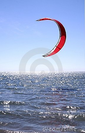Red Kite Surfer Sail against a blue sky hanging just above the surf.