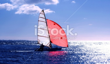 Red Sail, dinghy sailing into the sun on a blue sea
