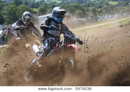 Dirt Bikes battle the corner in a cloud of mud